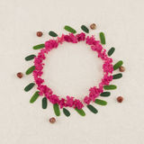 Round pink crape myrtle petals wreath. With green leaves with copy space royalty free stock photos