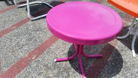 Round Pink Raspberry Metal Table on Concrete. Is a retro cool hipster end table stock images