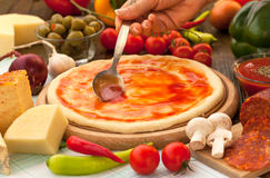 Round pizza dough with tomato sauce Stock Images