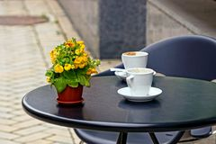Round plastic table on the street in a cafe with empty cups and a flowerpot. Empty white cups on a round table with a flowerpot royalty free stock photography