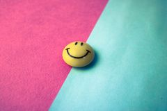 Round plastic yellow joyful smiling smiling toy round face Emoji on a pink blue violet background.  royalty free stock photo