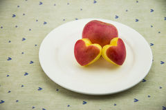 Round plate, Heart-shaped apple slices Stock Photo