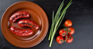 Round plate with toasted apetit sausages. With green onions and round tomatoes. Isolated on black background. The concept of traditional food.r Stock Photos