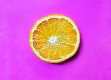 Round pomarańcze ciąca na lilym tle, w górę, selekcyjna ostrość, kopii przestrzeń obrazy royalty free