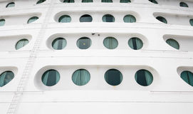 Round Porthole on Front of Ship. Round portholes and ladder on hull at front of a cruise ship Royalty Free Stock Images