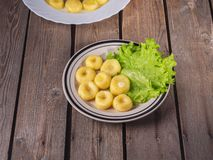 Round potatoe njeki on fresh lettuce leaves on a striped bright ceramic plate on a plank table. Round potato grains on fresh lettuce leaves on a striped bright royalty free stock photo