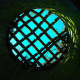Round prison hole with grid. Blue sky through the round prison window Stock Image