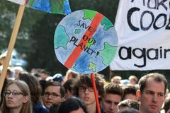 Round protest sign in the shape of planet earth saying `Save our planet` held up by young people during Global Climate Strike even