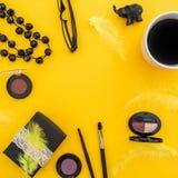 Round rama z prezenta pudełkiem, szkłami, kosmetykami, bijouterie i akcesoriami z kubkiem kawa na żółtym tle, Mieszkanie nieatuto Obraz Royalty Free