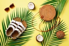 Round rattan torba, koks, birkenstocks, palmowe gałąź, okulary przeciwsłoneczni na żółtym tle sztandar Odgórny widok z kopią obrazy stock