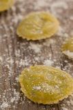 Round ravioli pasta dusted with floor on wooden background Stock Photos