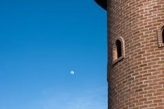 Round red brick block tower with  round window in blue clear sky. Round red brick block tower with round window in blue clear sky Stock Image