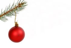 Round red Christmas ornament hanging from evergreen branch. Isolated on white stock image