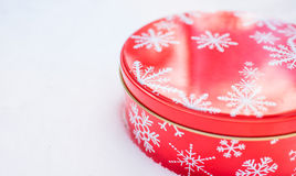 Round, red cookie and baked goods aluminum tin container decorated with white snowflake print pattern, resting on natural snow. Royalty Free Stock Images