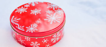 Round, red cookie and baked goods aluminum tin container decorated with white snowflake print pattern, resting on natural snow. Royalty Free Stock Image
