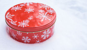 Round, red cookie and baked goods aluminum tin container decorated with white snowflake print pattern, resting on natural snow. Stock Image