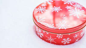 Round, red cookie and baked goods aluminum tin container decorated with white snowflake print pattern, resting on natural snow. Stock Images