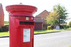 Red post box in UK. A round red ER post box in UK on a suburban street stock image