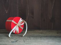 Round red gift box wrapped with festive ribbon on wooden background. Copy space royalty free stock photos