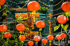 Round red paper lanterns hanging over a street in Singapore Stock Photos