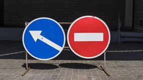 Round red road sign on metal pole. No Entry road-sign with a turn right or left sign. royalty free stock images