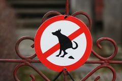 Round red sign on a park gate - here dogs are forbidden to poop and pee stock photos
