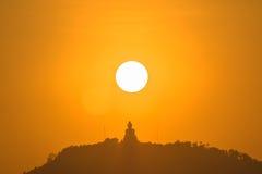 Round red sun above big Buddha Stock Photo