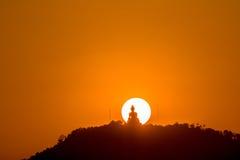 Round red sun above big Buddha Stock Images
