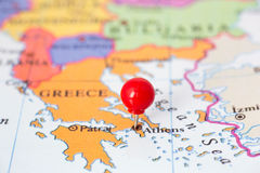 Red Pushpin on Map of Greece. Round red thumb tack pinched through city of Athens on Greece map. Part of collection covering all major capitals of Europe Stock Photos