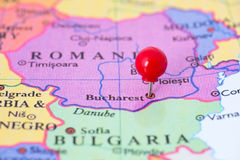 Red Pushpin on Map of Romania. Round red thumb tack pinched through city of Bucharest on Romania map. Part of collection covering all major capitals of Europe Royalty Free Stock Images