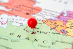 Red Pushpin on Map of France. Round red thumb tack pinched through city of Paris on France map. Part of collection covering all major capitals of Europe Royalty Free Stock Photography