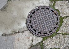 Round retro rusty pig-iron hatch of the old city sewerage Royalty Free Stock Image