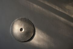 Round ribbed rosette on white wall with shadows Stock Photos