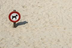 Traffic sign `forbidden for dogs` in sand stock images