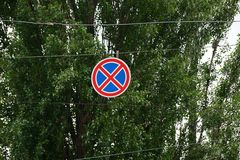 Round road sign on wires against the background of green branches Stock Image