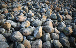 Round rocks. Rockery with lots of round stones close to the beach stock photo