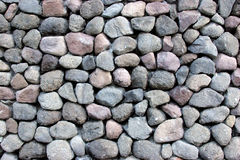 Round rocks stacked outside. A wall made of stacked round rocks Stock Image