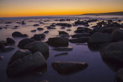 Sunset over rocky coastline Stock Photography