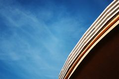 Round roof of building against the blue sky. Round roof of a modern building against the blue sky Stock Photo