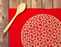 Round rope napkin or stand, red place mat  and spoon on a wooden Stock Image