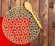 Round rope napkin or stand, red place mat  and spoon on a wooden Stock Photography