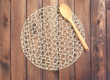Round rope napkin or stand and spoon on a wooden rustic table. T Stock Photography