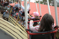 Round and Round. Kids and people on an amusement park ride Stock Image