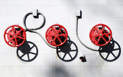 Round and Round and Round. Three red control wheels and their shadows against a white cinder block building Stock Photos