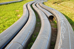 Round rubber tubes in perspective. Process of laying sewer pipe. Round rubber tubes in perspective on the background of green grass Royalty Free Stock Photos