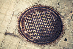 Round rusted hatch in urban pavement Royalty Free Stock Photos