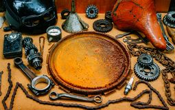 Round rusty board for logo, label or information in the center of tools, gears on vintage background. Motorcycle equipment and. Round rusty board for logo, label royalty free stock photo