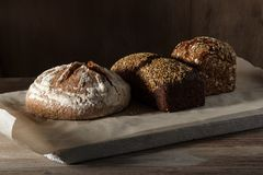 Round and rye black bread paper and wooden background.  Royalty Free Stock Image