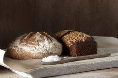 Round and rye black bread with salt on a wooden background.  Royalty Free Stock Image