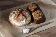 Round and rye black bread with sesame and a spoon of salt on paper.  Stock Image